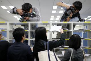 報道各社の棚に決算発表資料を入れる企業関係者(東京・日本橋兜町の東京証券取引所)【2015年10月撮影】