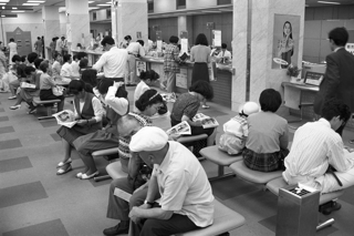 日銀の公定歩合引き下げに伴い、銀行や郵便貯金の金利が引き下げられる前に貯金しようとする人で込み合う郵便局の窓口(東京・京橋郵便局)【1991年7月撮影】