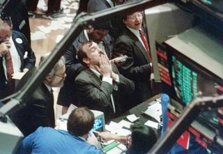 史上最大の下落幅を記録したニューヨーク証券取引所でぼうぜんとするディーラー【1987年10月撮影】